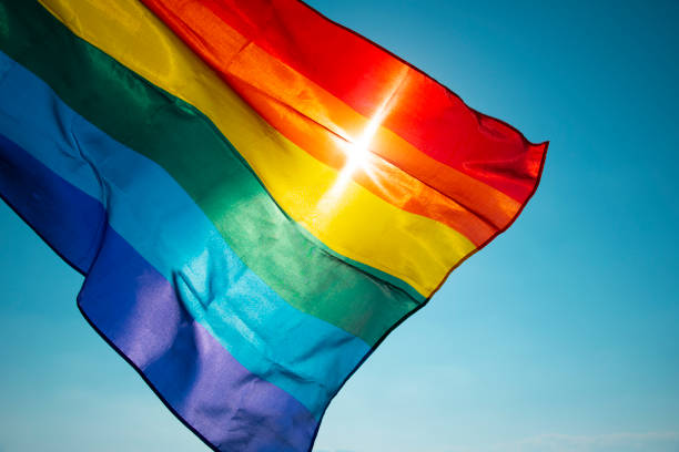 rainbow flag waving on the blue sky closeup of a rainbow flag waving on the blue sky, moved by the wind, with the sun in the background lgbtqi rights stock pictures, royalty-free photos & images