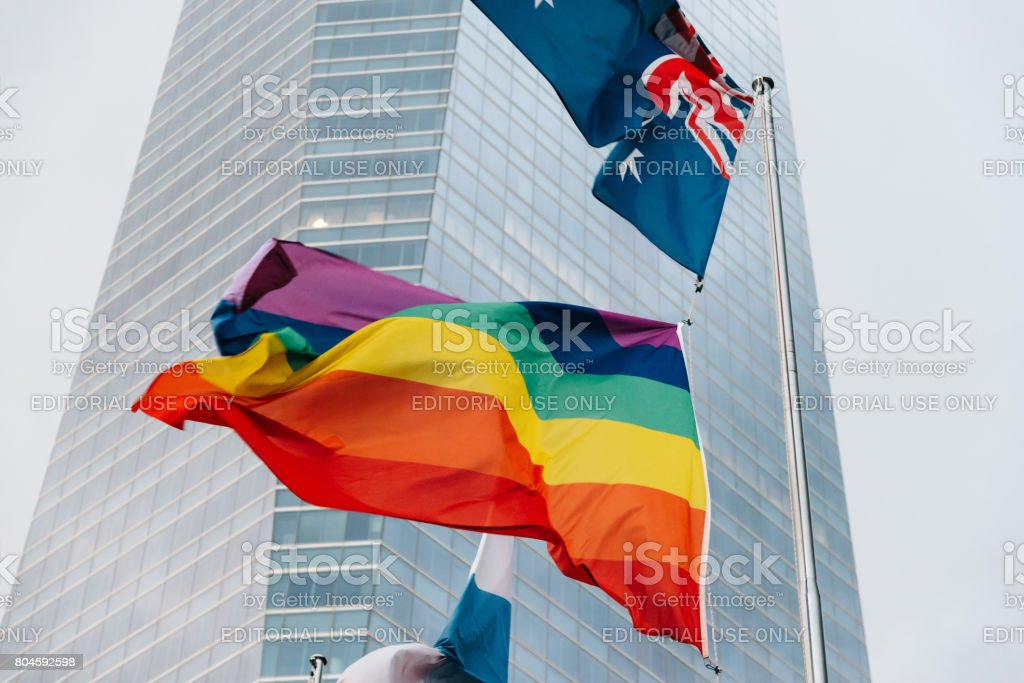 Rainbow flags waving against business buildings during Madrid World Pride 2017 stock photo