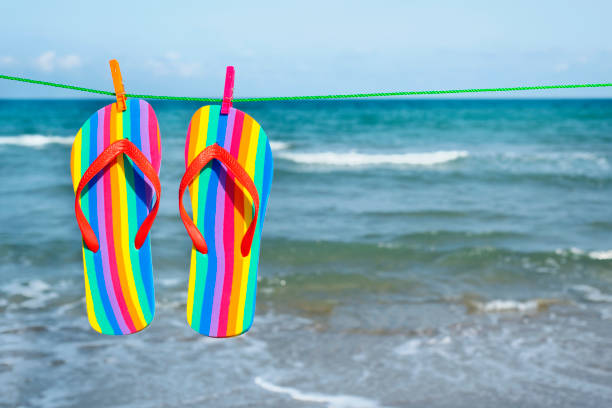 rainbow flip-flops hanging on a clothes line stock photo