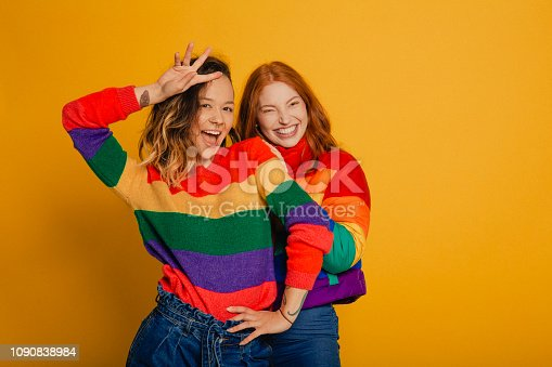 Portrait of a young redhead woman and a young mixed race woman both dressed in striped rainbow tops, standing in front of a yellow background.