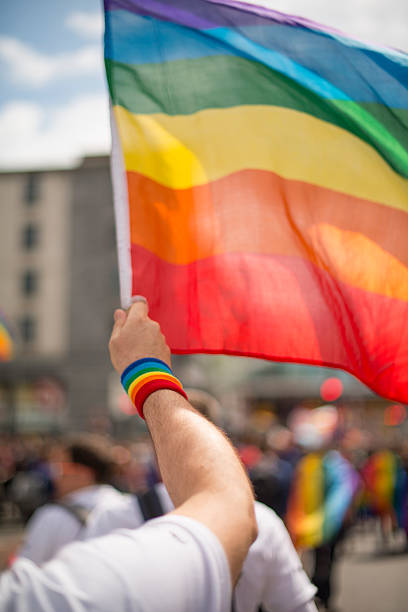 Rainbow gay pride flag and wristband in Pride Parade stock photo