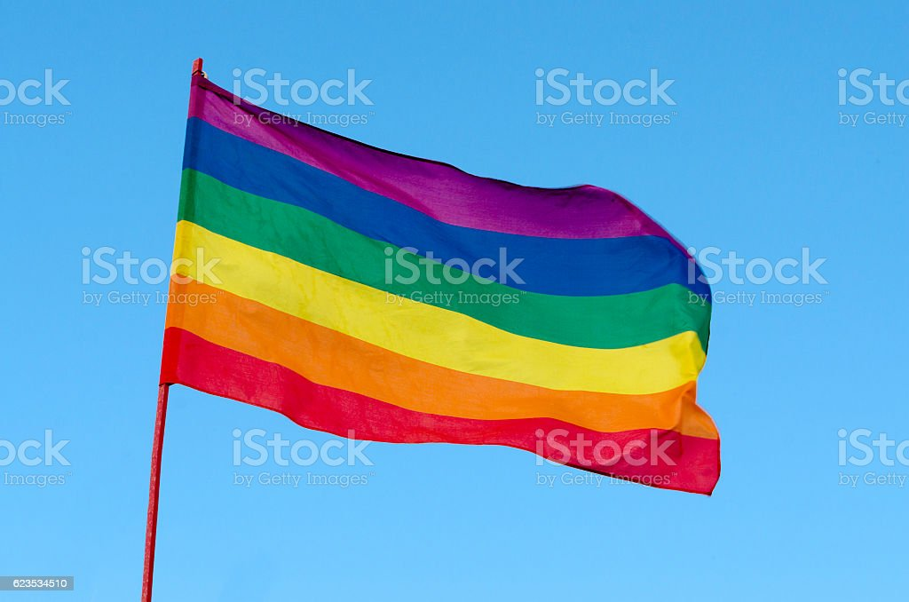 Rainbow Gay Pride Flag on blue sky background, USA stock photo