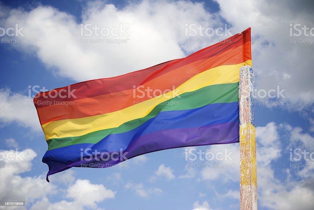 Rainbow Gay Pride Flag Waves in Stiff Breeze Summer Sky royalty-free stock photo