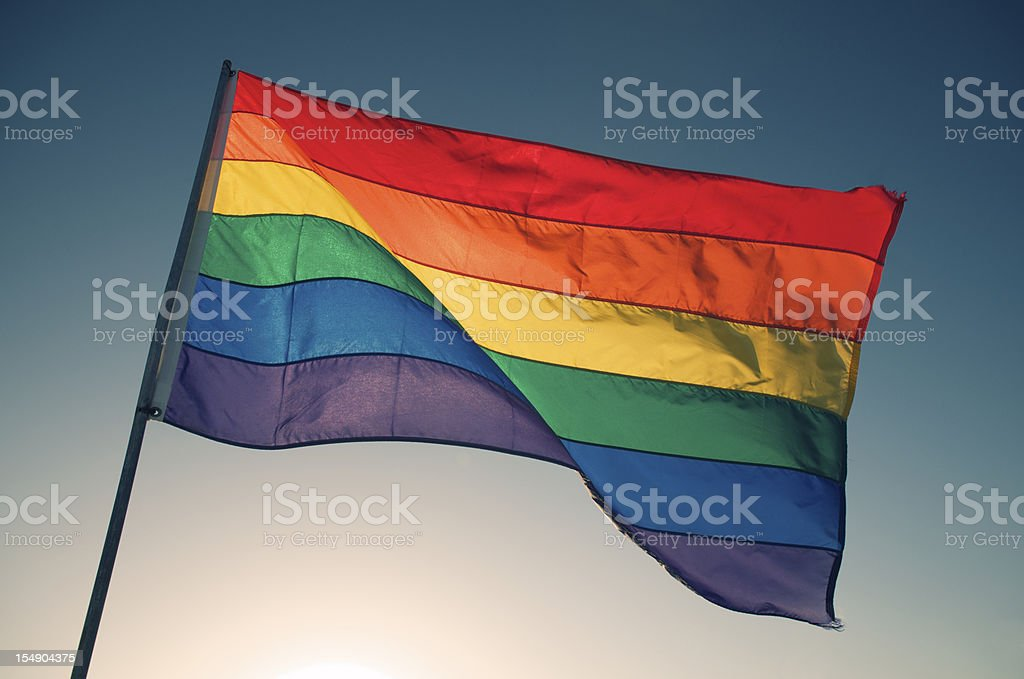 Rainbow Gay Pride Flag Waving Backlit by Bright Sun Sky stock photo