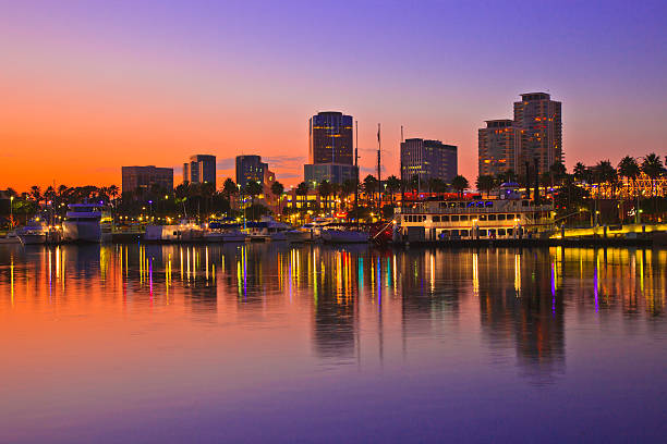 Rainbow Harbor, Long Beach, California illuminated at dusk Rainbow Harbor at Long Beach Marina with city skyline at sunset, California long beach california stock pictures, royalty-free photos & images