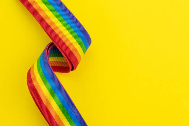 同性愛、レズビアン、ゲイ、トランスジェンダーの概念を祝うように使用してコピースペースを持つ固体黄色の背景に lgbt レインボーヘッドバンド - lgbtqi  ストックフォトと画像