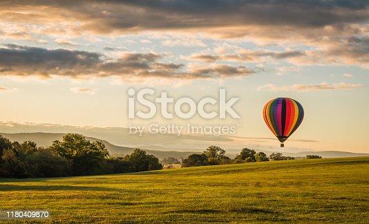 Rainbow hot-air balloon floats over grassy field and trees at sunrise, Pine Island, NY
