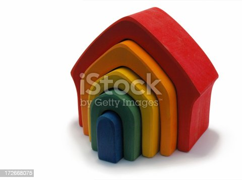 Isolated (pure white background) wooden house toy in colours of the rainbow - side angle.