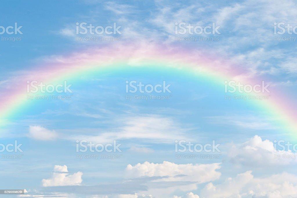 rainbow in blue sky stock photo