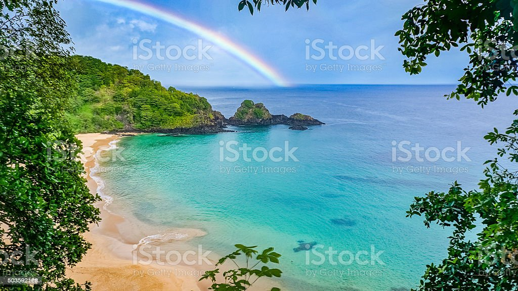 Rainbow in Praia do Sancho beach, Fernando de Noronha, Brazil stock photo