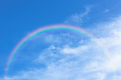 Rainbow and clouds against bright blue sky