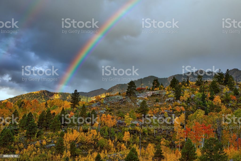 A rainbow is featured in this Colrado Autumn image overlooking a multicolored forest with an ominous cloudscape stock photo