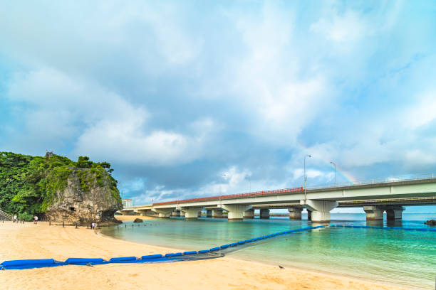Rainbow landscape of the Shinto Shrine Naminoue at the top of a cliff overlooking the Naminoue beach and bridge of Naha City in Okinawa Prefecture, Japan. Naha, Japan - September 15 2018: Rainbow landscape of the Shinto Shrine Naminoue at the top of a cliff overlooking the Naminoue beach and bridge of Naha City in Okinawa Prefecture, Japan. naha stock pictures, royalty-free photos & images