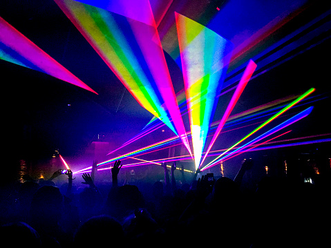 Colourful neon laser lights in a nightclub with silhouette of people.