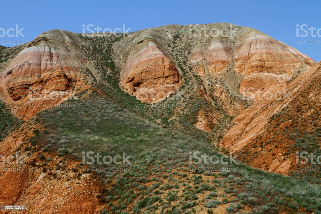 Rainbow mountains with the green grassy slope stock photo