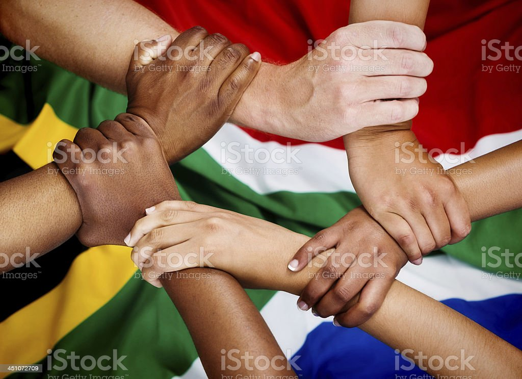 Rainbow Nation hands clasped in unity against South African flag stock photo