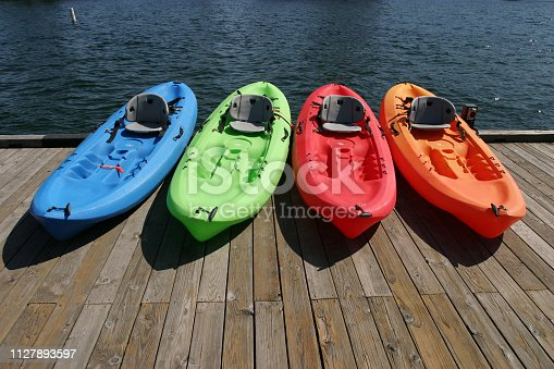 A rainbow of kayaks sitting on a lake dock