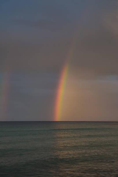 Regenbogen am wolkenverhangenen Himmel am Meer – Foto
