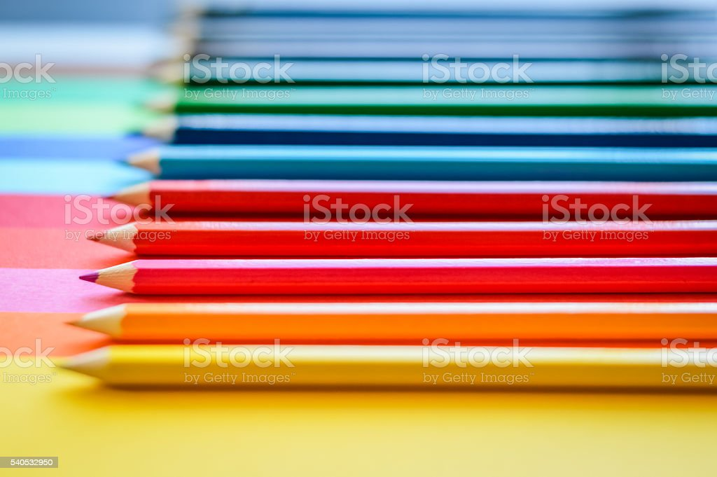 rainbow ordered pencils on colored papers stock photo