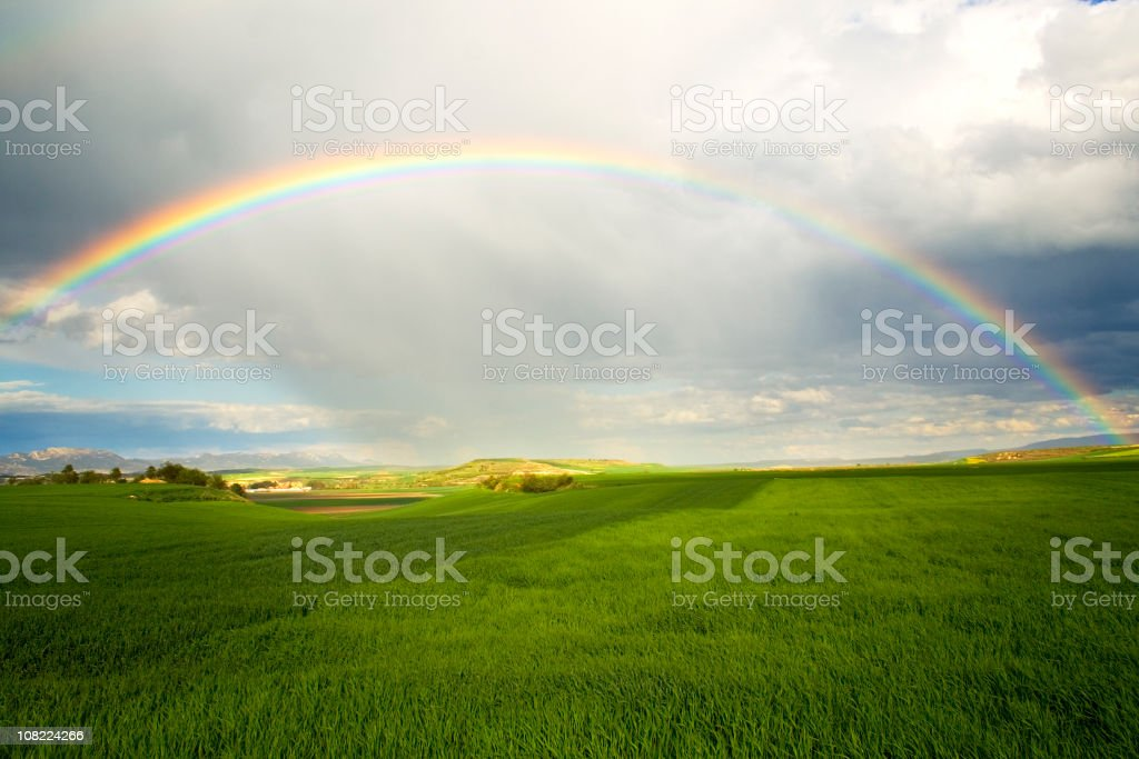 A rainbow over a green field with rain clouds stock photo