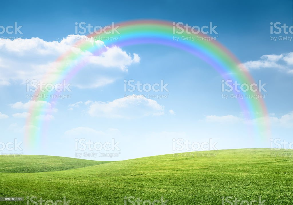 Rainbow over idyllic hilly landscape stock photo