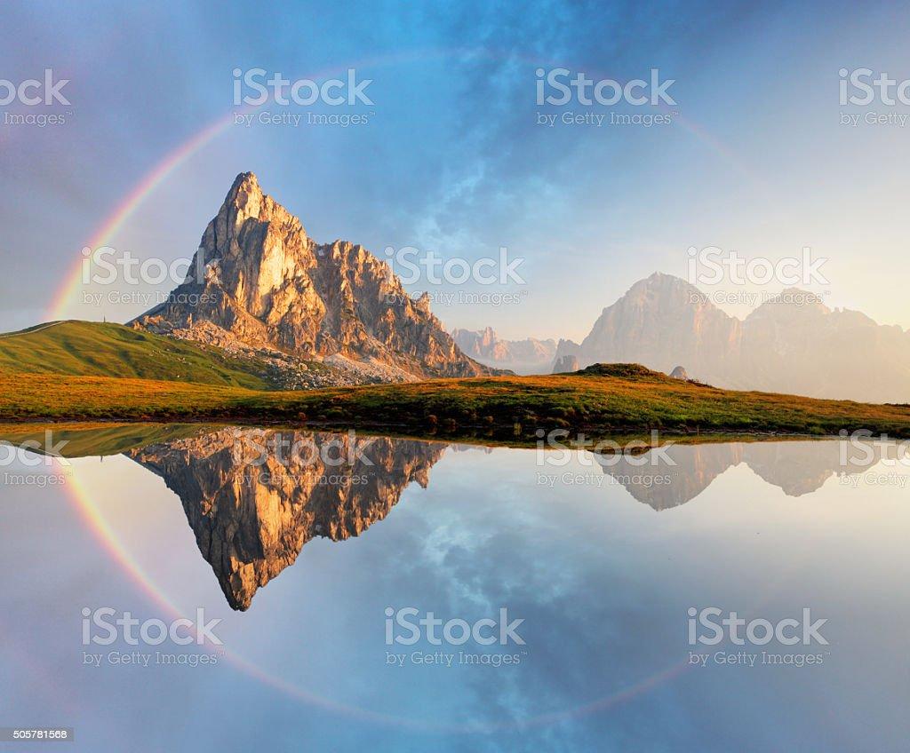 Rainbow over Mountain lake reflection, Dolomites, Passo Giau stock photo