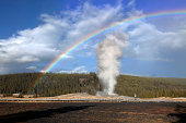 Old Faithful is a cone geyser located in state of Wyoming, Yellowstone National Park in the United States. It is erupting on average every ninety minutes. Full rainbow appeared when the rainstorm passed by.