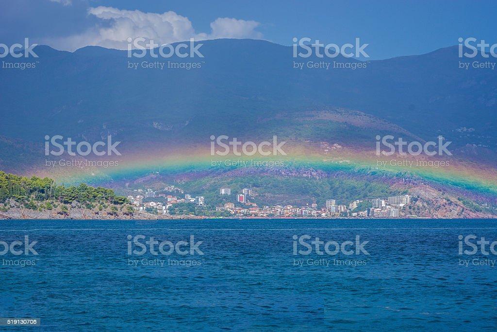 Rainbow over small coastline town. stock photo