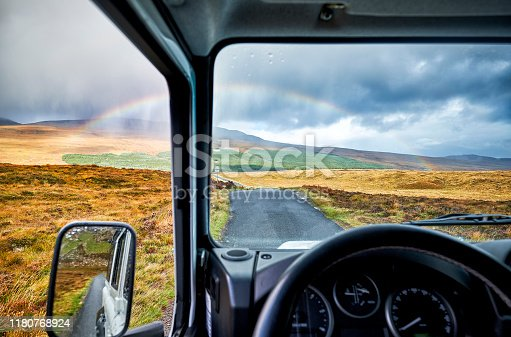 A rainbow over the landscape in scotland seen from a 4x4 car along the route of the north coast 500. The road leads through the landscape.