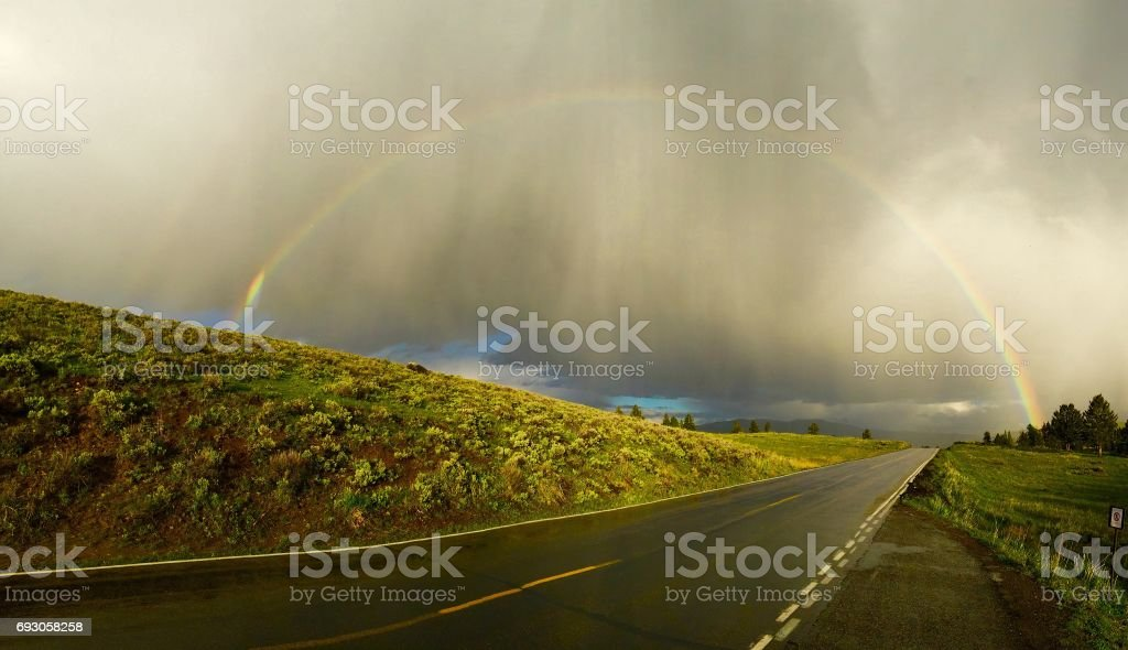 rainbow over the road on a cloudy day stock photo