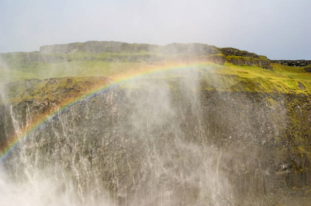 Rainbow over the water of the Dettifoss waterfall stock photo