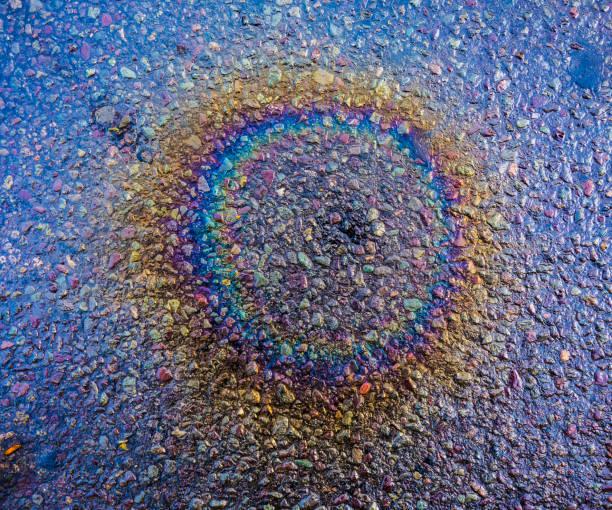 regenbogen benzin flecken auf straße - disaster design stock-fotos und bilder