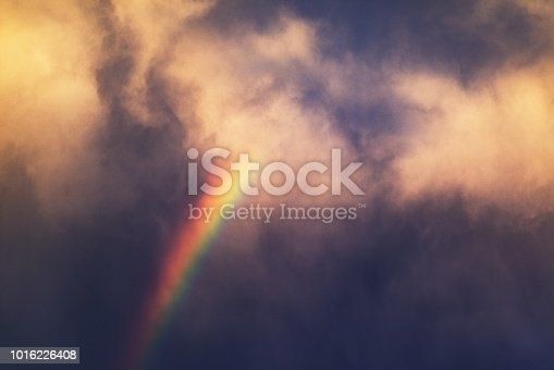 Bright rainbow amidst dramatic clouds.