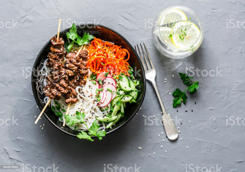 Rainbow power buddha bowl. Asian style beef skewers, rice vermicelli, pickled vegetables salad carrots, cucumbers, radishes, greens and lemon thyme lemonade on grey background, top view stock photo