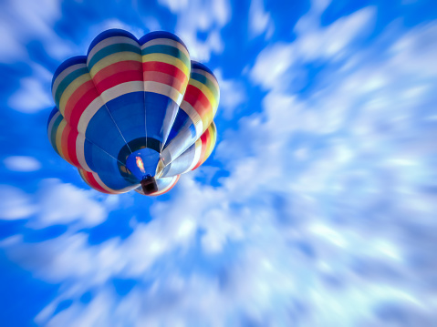 Rainbow striped hot air balloon flying high into the blue sky above giving a sense of freedom and letting go
