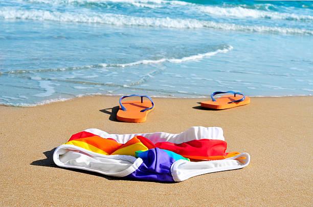 rainbow badeanzug und flip-flops in dem sand von einem strand - fkk strand stock-fotos und bilder