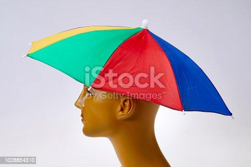 Rainbow umbrella as hat on man's head
