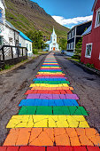 Colorful rainbow walkway leading to a little church in the picturesque town of seydisfjordur in the East Fjord of Iceland