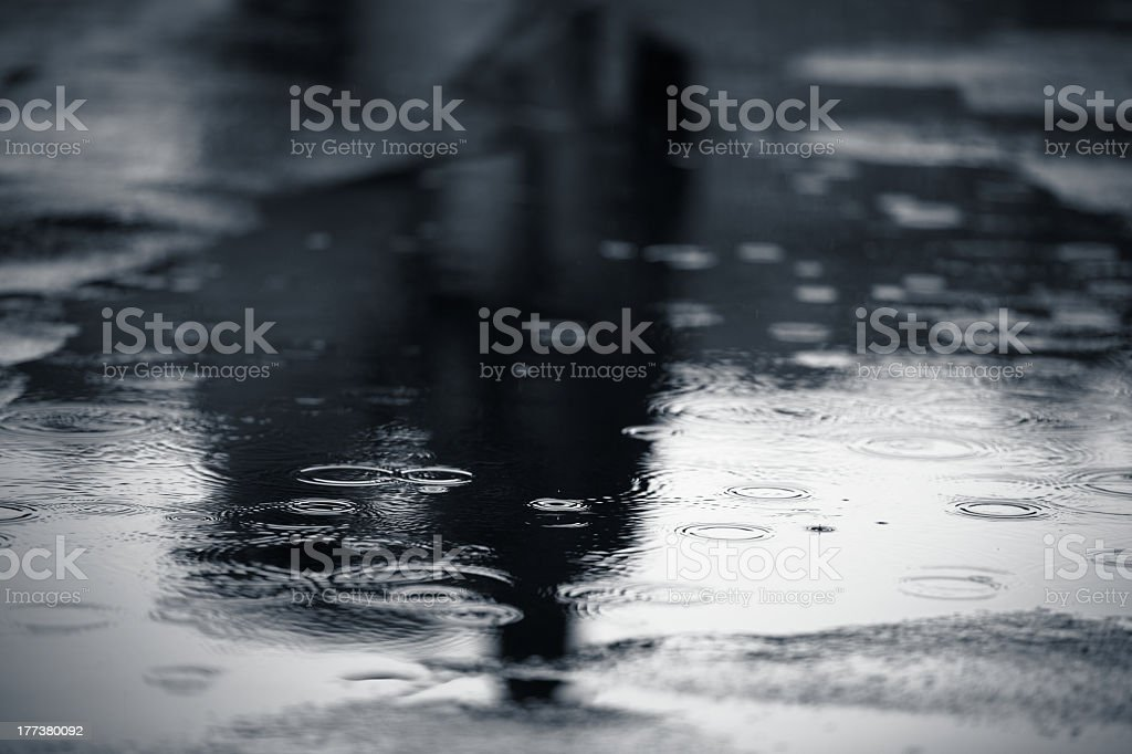 Raindrops falling onto puddles in street stock photo