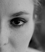 Single teardrop falling from brown-eyed girl