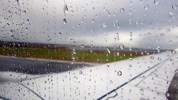 Raindrops on airplane window by the runway. stock photo