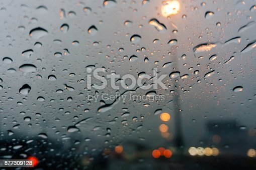 1054750504 istock photo Raindrops on car window closeup blurry background 877309128