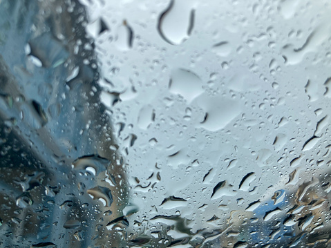 raindrops on car's front windshield and blurred blue buildings and gray sky view on background