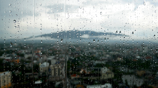 Raindrops on the window and the mountain with the city in blur background.