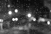 Raindrops on window close-up in black and white. Seasonal background and texture for design and ideas.