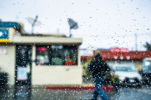 Raindrops on the windshield; Person walking outside during rainy weather in the background; California