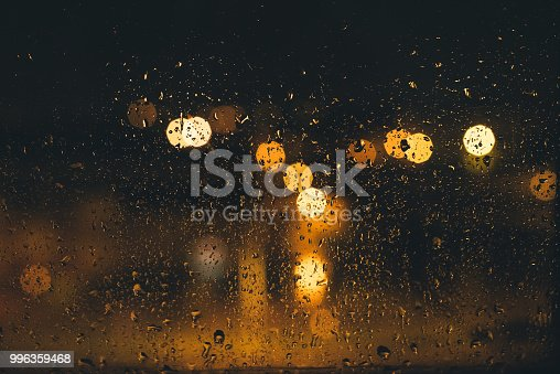 Out of focus city lights at night seen through window covered with raindrops during the rainfall.