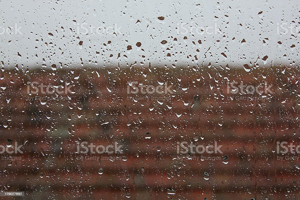 Raindrops on window glass with wet roof - weather background royalty-free stock photo