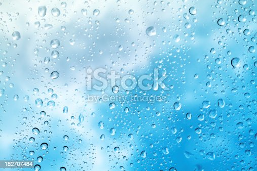 Raindrops on window with clouds.  Blue hue added.
