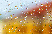 Large raindrops on the windshield of car. Bright building reflected in raindrops on glass. Abstract background. Selective photo
